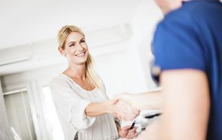 A woman shaking hands with a dentist.