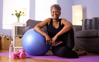 Smiling older woman on exercise mat