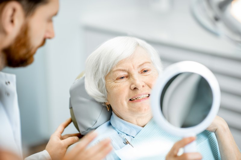 an older lady in the dentist chair looking at her smile