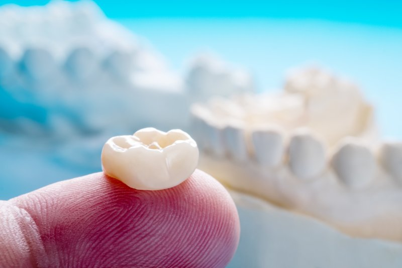 Close-up of prosthodontist in Lincoln holding crown on finger