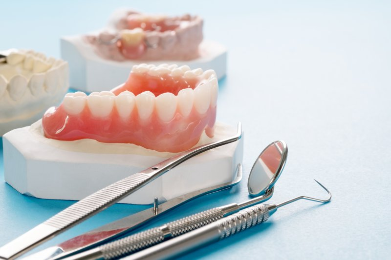 Dental tools lying next to dentures